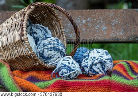 Blue And White Wool Balls In A Wicker Basket On A Multi-colored Knitted Blanket. Natural Background.