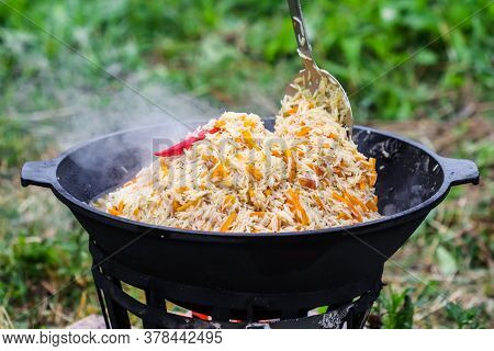Cooking Rice Pilaf In A Large Cast-iron Pot On Fire