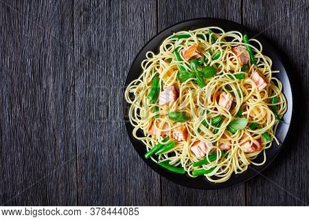 Spaghetti With Green Bean And Roasted Salmon Pieces, Decorated With Fresh Basil Leaves, Served On A