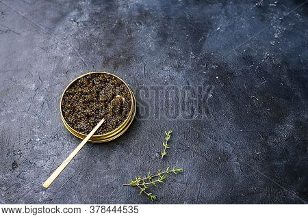Black Sturgeon Caviar With A Black Spoon And A Dark Background. A Place For Text, A View From Above.