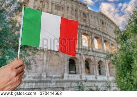 Man Is Holding Italian Flag In Hand. Colosseum In Background. Travel In Italy Concept.