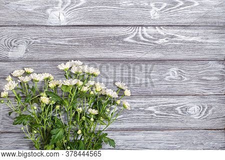 A Bouquet Of White Bush Chrysanthemums On A Wooden Table