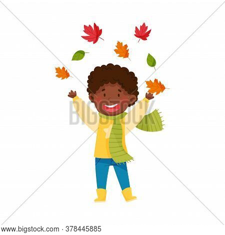 Funny African American Boy Character In Rubber Boots And Scarf Throwing Autumn Leaves Vector Illustr