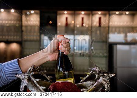 Hand Hold Wine Bottle In Ice Bucket. Wine Bottle In Bucket With Ice. Champagne Bottle In Ice Bucket