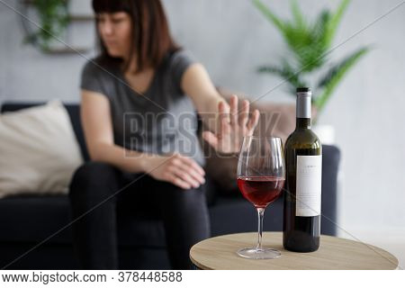 Healthy Lifestyle Concept - Young Woman Refusing Glass Of Red Wine With Open Palm Gesture