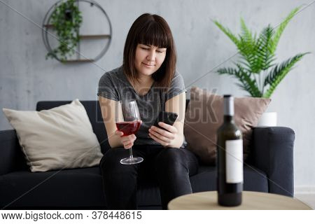 Portrait Of Young Woman Drinking Red Wine And Using Smartphone At Home
