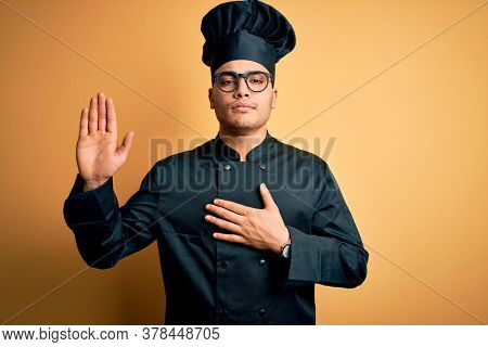 Young brazilian chef man wearing cooker uniform and hat over isolated yellow background Swearing with hand on chest and open palm, making a loyalty promise oath