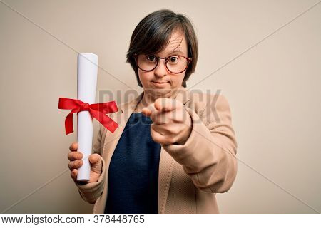 Young down syndrome business woman holding univeristy diploma award over isolated background pointing with finger to the camera and to you, hand sign, positive and confident gesture from the front