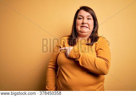 Beautiful brunette plus size woman wearing casual sweater over isolated yellow background Pointing aside worried and nervous with forefinger, concerned and surprised expression