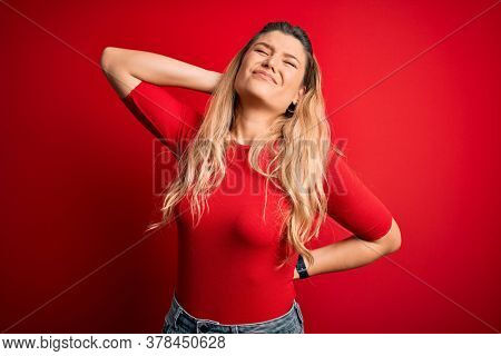 Young beautiful blonde woman wearing casual t-shirt standing over isolated red background Suffering of neck ache injury, touching neck with hand, muscular pain