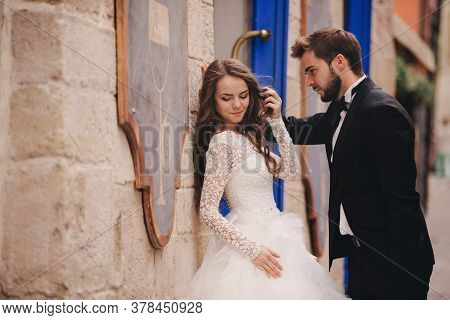 Wedding Couple Hugging In The Old City. Blue Vintage Doors And Cafe In Ancient Town On Background. S