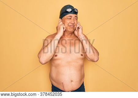Middle age senior grey-haired swimmer man wearing swimsuit, cap and goggles covering ears with fingers with annoyed expression for the noise of loud music. Deaf concept.