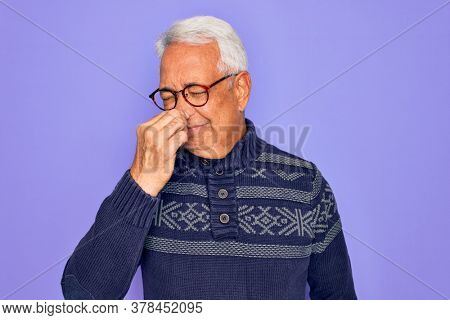 Middle age senior grey-haired man wearing glasses and winter sweater over purple background smelling something stinky and disgusting, intolerable smell, holding breath with fingers on nose. Bad smell