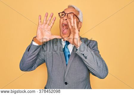 Middle age senior grey-haired handsome business man wearing glasses over yellow background Shouting angry out loud with hands over mouth
