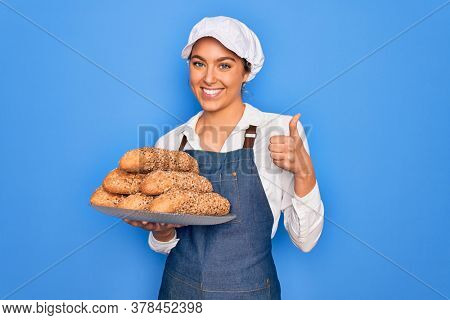 Young beautiful blonde baker woman with blue eyes holding tray with wholemeal bread cereal happy with big smile doing ok sign, thumb up with fingers, excellent sign