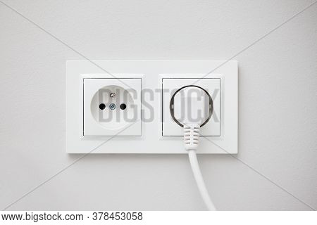 Electrical Socket Isolated On Gray Wall. White Wire Plug Plugged In. Renovated Studio Apartment Powe