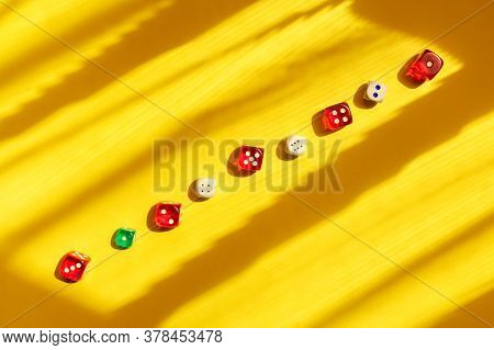 Dice Diagonal On A Yellow Background, Beautiful Light And Shadows. Playing A Game With Dice. Rolling