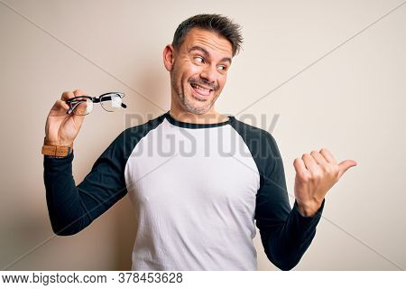 Young handsome optical man showing glasses standing over isolated white background pointing and showing with thumb up to the side with happy face smiling