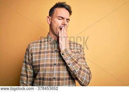 Young handsome man wearing casual shirt standing over isolated yellow background bored yawning tired covering mouth with hand. Restless and sleepiness.