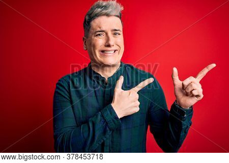 Young handsome modern man wearing elegant green shirt over red isolated background Pointing aside worried and nervous with both hands, concerned and surprised expression