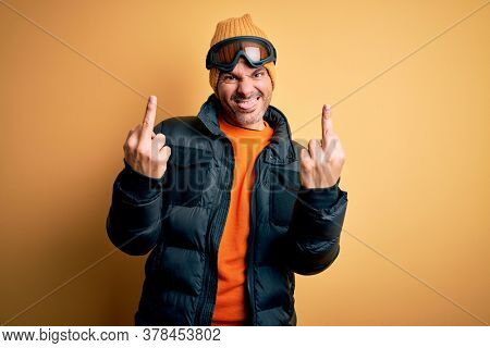 Young handsome skier man skiing wearing snow sportswear using ski goggles Showing middle finger doing  bad expression, provocation and rude attitude. Screaming excited