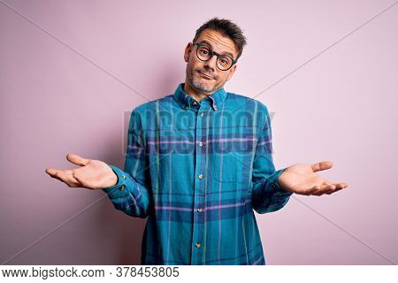 Young handsome man wearing casual shirt and glasses standing over isolated pink background clueless and confused expression with arms and hands raised. Doubt concept.