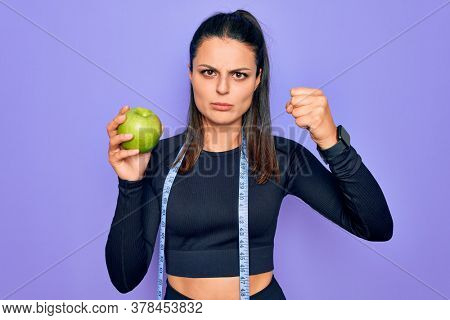 Beautiful brunette sporty woman using tape measure eating apple fruit over purple background annoyed and frustrated shouting with anger, yelling crazy with anger and hand raised
