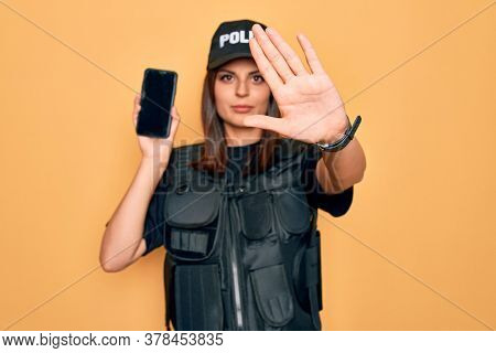 Beautiful brunette policewoman wearing police uniform holding smartphone showing screen with open hand doing stop sign with serious and confident expression, defense gesture