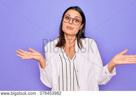 Young beautiful brunette psychologist woman wearing coat and glasses over purple background clueless and confused expression with arms and hands raised. Doubt concept.