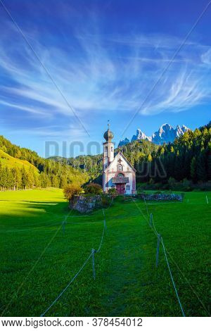 Majestic Dolomites. The Val di Funes Valley. Beautiful picturesque church of Santa Maddalena on the sunset. Italy, Tyrol. The concept of active, ecological and photo tourism
