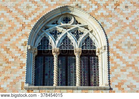 Ornate semicircular window. Decor element of  Doge's Palace. Palazzo Ducale is a great monument of Italian Gothic architecture. Magical journey to Venice. The concept of cultural and photo tourism