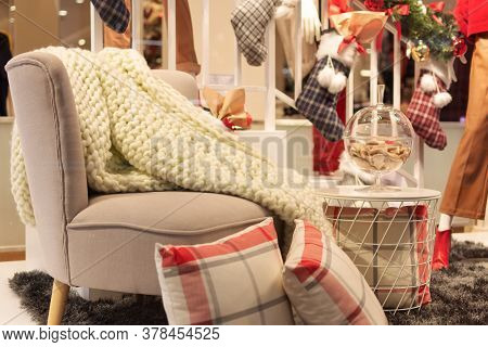 Cozy Interior Room Decorated For Christmas. An Empty Chair With Warm Plaid. Home Comfort Of Modern H