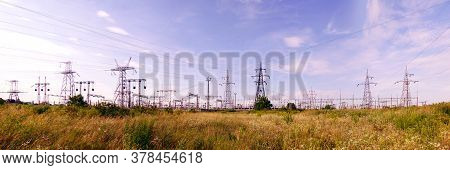 Panoramic Image Of High Voltage Substation. Distribution Electrical Power. Silhouettes Of Pylons And