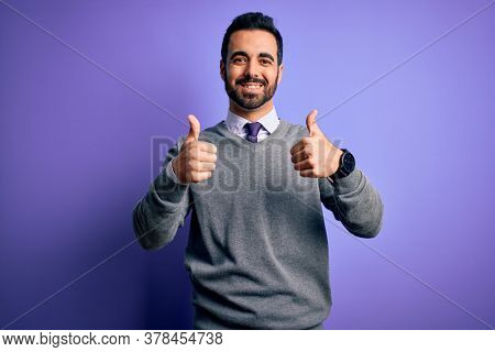 Handsome businessman with beard wearing casual tie standing over purple background success sign doing positive gesture with hand, thumbs up smiling and happy. Cheerful expression and winner gesture.