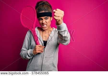 Young african american sportswoman playing tennis using racket over isolated pink background annoyed and frustrated shouting with anger, crazy and yelling with raised hand, anger concept