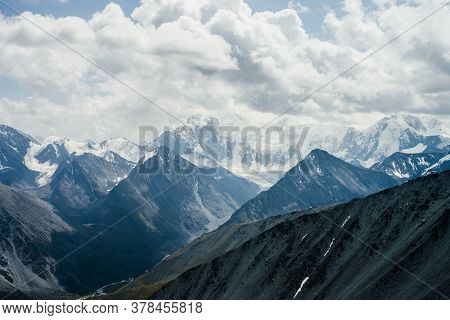 Awesome Dramatic Alpine Landscape With Beautiful Huge Glacial Mountains Under Gray Cloudy Sky. Wonde