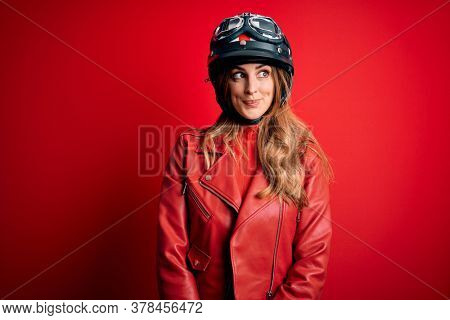 Young beautiful brunette motrocyclist woman wearing moto helmet over red background smiling looking to the side and staring away thinking.