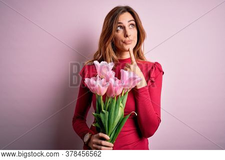 Young beautiful brunette woman holding bouquet of pink tulips over isolated background Thinking concentrated about doubt with finger on chin and looking up wondering