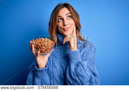 Young beautiful brunette woman holding bowl german baked pretzels over blue background serious face thinking about question, very confused idea