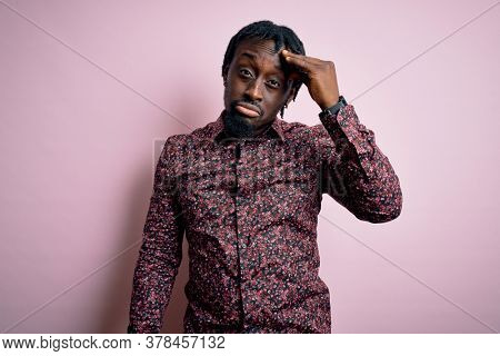 Young handsome african american man wearing casual shirt standing over pink background worried and stressed about a problem with hand on forehead, nervous and anxious for crisis