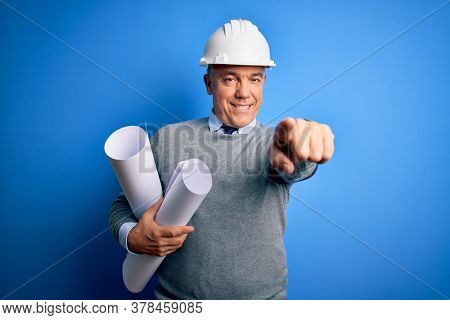 Middle age handsome grey-haired architect man wearing safety helmet holding blueprints pointing to you and the camera with fingers, smiling positive and cheerful