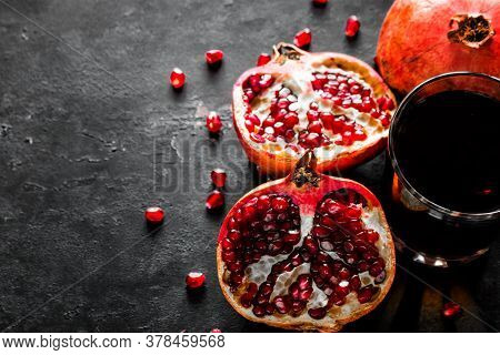 Pomegranate Juice In A Glass And Pomegranate With Seeds On A Black Background With Place For Text