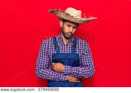 Young latin man wearing farmer hat and apron with hand on stomach because indigestion, painful illness feeling unwell. ache concept.