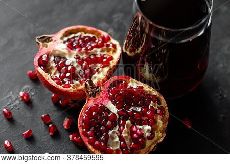 Freshly Squeezed Pomegranate Juice On A Black Background And A Pomegranate Fruit