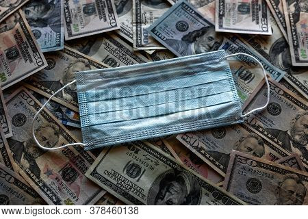 Medical Mask On The Background Of Dollar Bills, Concept Crisis, Pandemic, Inflation