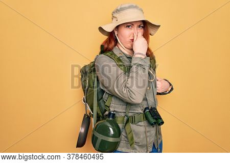Young redhead backpacker woman hiking wearing backpack and hat over yellow background smelling something stinky and disgusting, intolerable smell, holding breath with fingers on nose. Bad smell