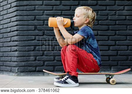 Young Skater Sit On Skateboard, Drink Fresh Water From Reusable Bottle After Children Training Class