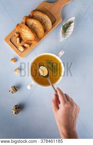 Chicken Bouillon With Dill And Quail Eggs. Baguette Toasts And Croutons On Bamboo Cutting Board. Wom