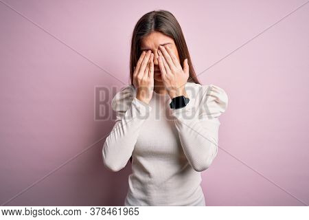 Young beautiful woman with blue eyes wearing casual white t-shirt over pink background rubbing eyes for fatigue and headache, sleepy and tired expression. Vision problem