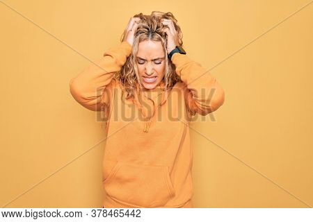 Young beautiful blonde sporty woman wearing casual sweatshirt over yellow background suffering from headache desperate and stressed because pain and migraine. Hands on head.